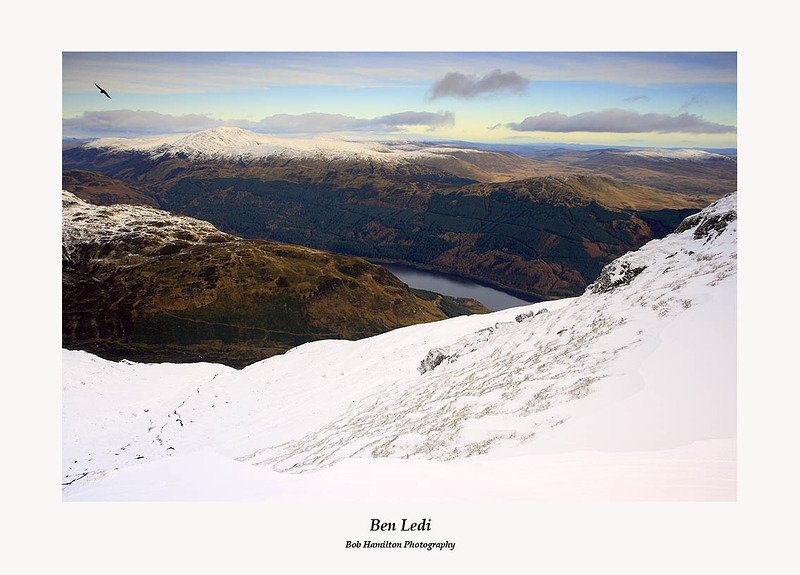 A raven flies over the snowy slopes of Ben Ledi with Loch Lubnaig and Beinn Each in the background